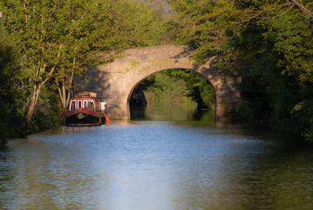 Narrow boats on River Avon with stone bridge. Springtime scene with in warm evening sun on the outskirts of Bath, in Somerset, UK