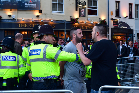 hundreds and thousands: CARDIFF, UK - 3 JUNE 2017 Man arrested by police during Champions League Final. British police and security services on high alert as hundreds of thousands of fans enjoy football in the capital of Wales