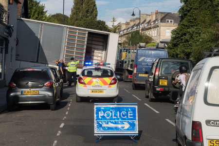 inconvenience: BATH, UK - 01 SEP 2017 Lorry stuck on steep hill with driver and police and sign. HGV unable to move after attempting a sharp turn off London Road, causing police response and traffic chaos Editorial