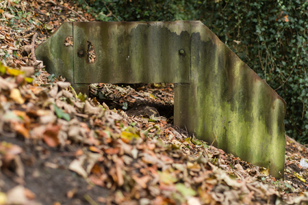 Ruined Anderson shelter rusted and partially buried, front. World War Two bomb shelter showing exposed corrugated iron sheets and steel plates Stock Photo
