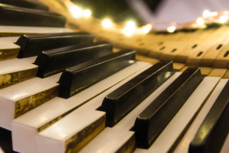 Old piano keyboard twisted with keys pushed down. Keys removed from the body of musical instrument lit up as a Christmas decoration Stock Photo