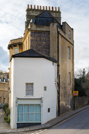 BATH, UK - FEB 12 2018 The Old Red House ghost sign in Bath, UK. Building in the UNESCO World Heritage Site with paint from historical business, on Rivers Street