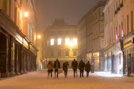 BATH, UK - MARCH 01 2018 The High Street at night in snow, with people walking. Shopping and eating area in UNESCO World Heritage city after unusually heavy snowfall