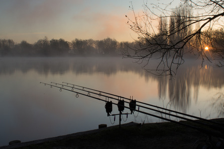 Sunrise over a lake with a silouhette of carp fishing rods
