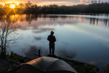 Zonsopgang met een Carp Angler met uitzicht op het meer