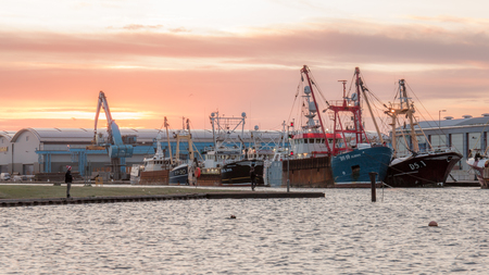 22nd October 2017; Shoreham Port, Sussex, UK; two men fish in the harbour in front of a fleet of fishing trawlers. There is a colourful dawn sky Editorial