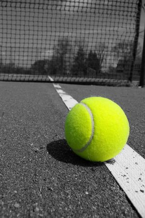 color tennis ball on black and white court Stock Photo