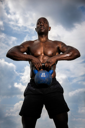 kettle bell: Black male with muscles lifting heavy kettle bell