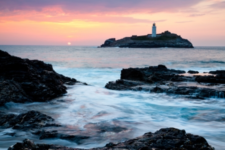 Sunset on the cliffs at Godrevy with Godrevy Island and Lighthouse in the background.