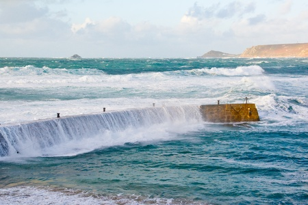 breakwaters: Storm waves crashing over the breakwater at Sennen Cove Cornwall England UK Stock Photo