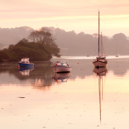 Boats moored on the river at Penryn Cornwall England UK photo
