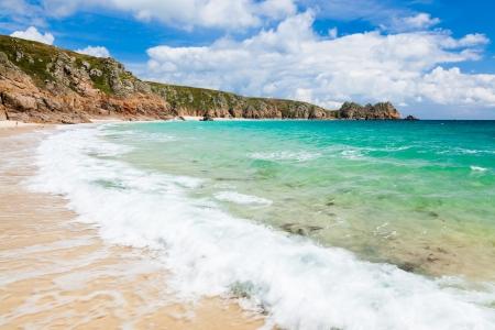 porthcurno: Wave crashing on the golden sandy beach at Porthcurno Cornwall England UK Stock Photo