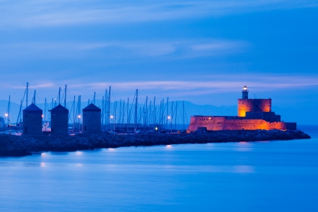 Night shot of the windmills and lighthouse at Mandraki harbour Rhodes Greece