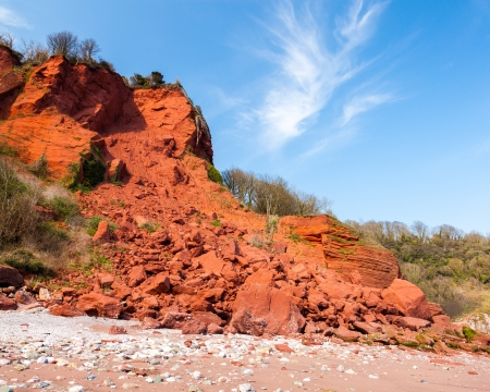 coastal erosion: Fallen red sandstone cliffs  Coastal Erosion  at Oddicombe Beach Devon England UK