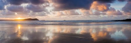 Dramatic reflections on the beach at New Polzeath Cornwall England UK