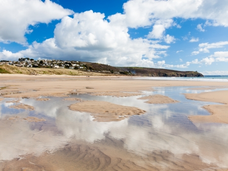 Beautiful sky reflected in pools of water on the beach at Praa Sands Cornwall England photo
