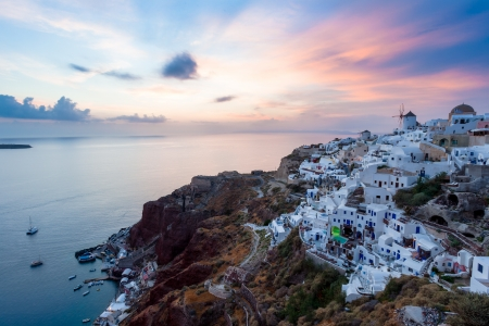 Vibrant sunset over houses and villas at Oia Santorini Greece