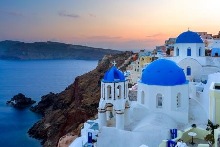 サントリーニ島イア ギリシャで青いドーム教会上の夕暮れ