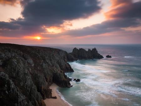 Dramtic sunrise over Pednvounder Beach and Logans Rock from Treen Cliffs near Porthcurno Cornwall England UK