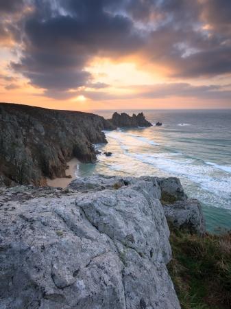 porthcurno: Dramtic sunrise over Pednvounder Beach and Logans Rock from Treen Cliffs near Porthcurno Cornwall England UK