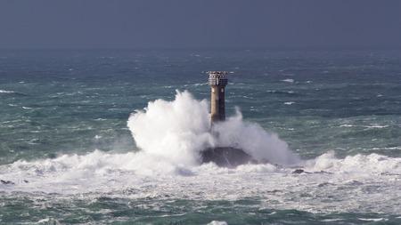 Huge waves crashing Longships Lighthouse photographed from Lands End Cornwall England UK photo