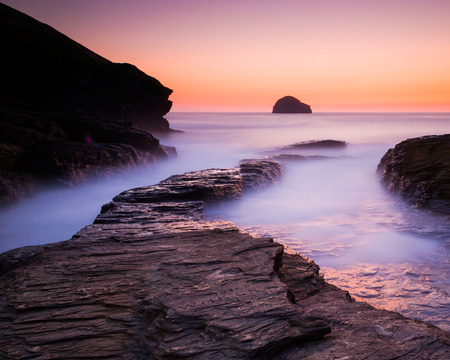 Vibrant afterglow illuminates the wet rock at Trebarwith Strand on the North Cornwall Coast.