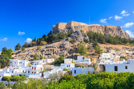White washed houses with the castle above at Lindos on the Greek Island of Rhodes Greece Europe Stock Photo