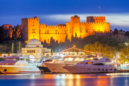 Hafen von Mandraki Rhodos Griechenland und der Großmeisterpalast in der Nacht.