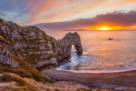jurassic: Sunset at Durdle Door natural limestone arch on the Jurassic Coast near Lulworth in Dorset England UK Europe