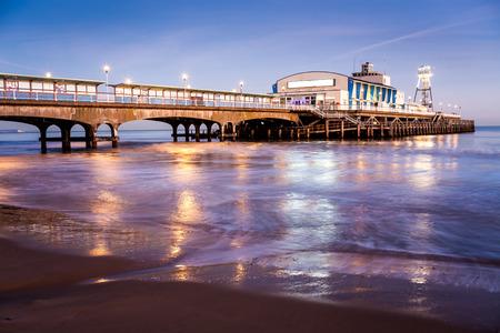 ボーンマスの夜のライトは、ビーチでの濡れた砂に反映されます。ドーセット英国英国ヨーロッパ。