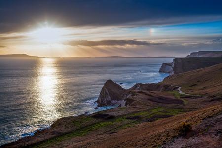 durdle door: The sun setting on the coastpath between Lulmorth Cove and Durdle Door Dorset England UK Europe