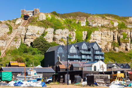 Beachside buildings with Hastings East Cliff Funicular Railway above. East Sussex England UK Europe