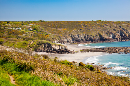 On the coast path approaching the Sandy beach at Kennack Sands on the Lizard Peninsula Cornwall England UK Europe