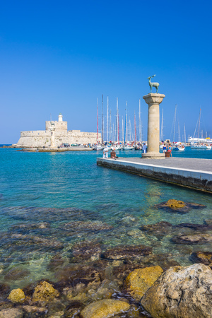 RHODES TOWN, RHODES, GREECE July 24 2015 The entrance to the historic Mandraki Harbour Rhodes Greece Europe