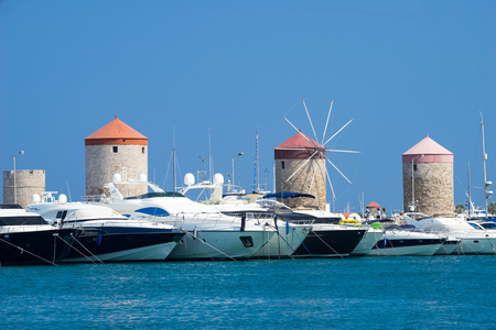 RHODES TOWN, RHODES, GREECE July 24 2015 historic windmills and luxury yachts in Mandraki Harbour Rhodes Greece Europe