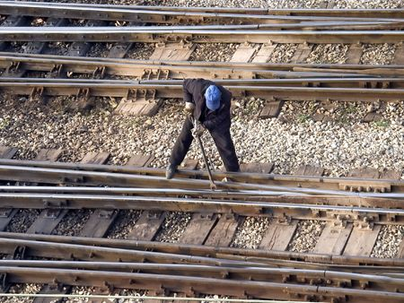 Maintenance worker fixing railway switch bolts Stock Photo