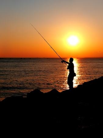 Fisherman silhouette on sunset photo