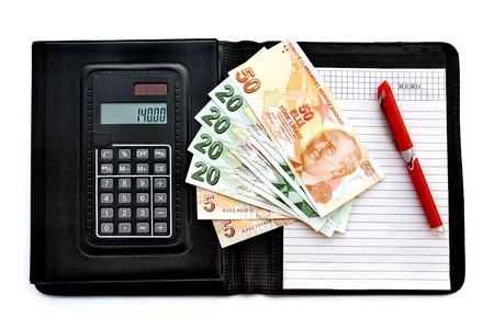 Leather covered calculator memo pad with banknotes and a pen on white background