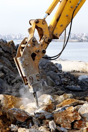 A hydraulic arm with impact breaker in action 스톡 사진