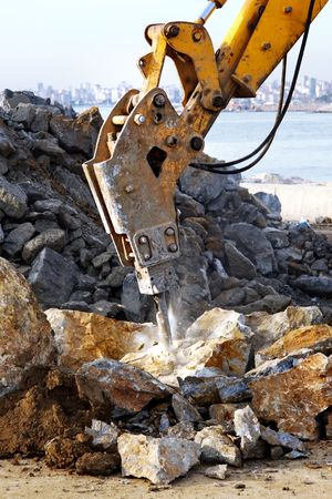 A hydraulic digger breaking up rock