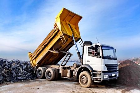 Een dump truck is dumping grint op een opgraving site