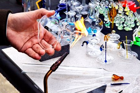 glassblower: Artist hand heats up the glass.