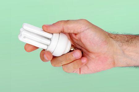 Hand holding energy saver lamp photo