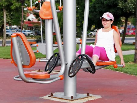 gymnasium: Girl exercising on exercise equipment