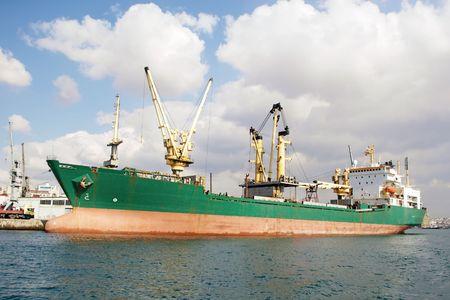 docked: Green bulk carrier ship docked in harbor Stock Photo