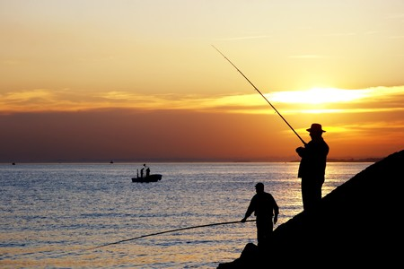 resting rod fishing: Silhouettes of fisherman against sunset