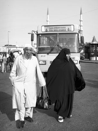 TURKEY - JUNE 10: An Elderly Muslim couple in traditional black and white costumes look for their bus stop at Eminonu square