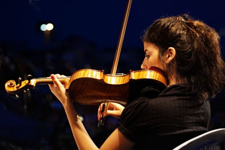 playing folk: ISTANBUL - JULY 11: Members of the Maltepe Symphonic Orchestra perform live at Maltepe open air stage. Musician playing violin.