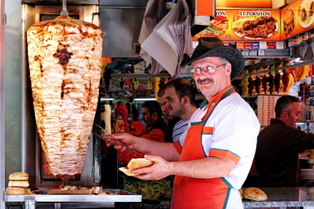 turkish man: ISTANBUL - APRIL 30: Cheerful man cooks and sells kebab in a small buffet at Eminonu region on April 30, 2010 in Istanbul