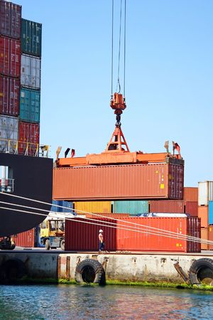 Freight container hanging on crane at sea port Stock Photo